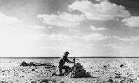 Um aviador da RAF coloca uma cruz, feita a partir dos destroços de uma aeronave, sobre um túmulo em 27 de dezembro de 1940, contendo os corpos de cinco militares da Força Aérea italiana derrubados na Batalha do Deserto em Mersa Matruh em 31 de outubro de 1940