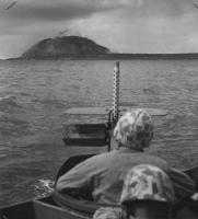 """Além do cano da arma de uma barcaça de desembarque a Guarda Costeira sob o ameaçador Monte Suribachi, o vulcão na ponta sul de Iwo Jima. Fortificada pelos japoneses, os lados Suribachi com cavernas incrustadas irrompeu com fogo mortal quando os fuzileiros navais invadirama partir das praias em 19 de fevereiro. O dia histórico quando a força-tarefa da marinha chutou a """"porta da frente"""" de Tóquio."""