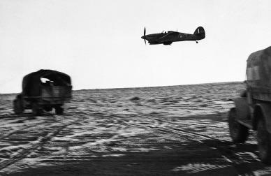 A baixa altitude avião da Real Força Aérea escolta caminhões de uma unidade da Nova Zelândia pelo Egito, em 03 agosto de 1942.