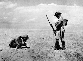 Um oficial alemão ferido, encontrado no deserto do Egito durante os primeiros dois dias de uma ofensiva britânica. É vigiado por uma sentinela, em 13 de novembro de 1942.