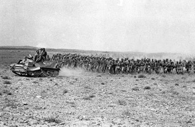 Dois mil prisioneiros italianos marcham de volta através das linhas Oitavo Exército, liderados por uma viatura com armas Bren, no deserto da Tunísia, em março de 1943.