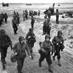 Enfermeiras dos EUA caminham ao longo de uma praia na Normandia, França, em 04 de julho de 1944. Elas estão a caminho de hospitais de campanha para cuidar dos soldados feridos. (AP Photo).