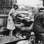 A luta do homem e da mulher francesa, com armas alemães capturadas como civis e membros das Forças francesas do Interior combateu os alemães, em Paris, em agosto de 1944, antes da rendição das forças alemãs e de Libertação de Paris em agosto 25. (AP Photo)