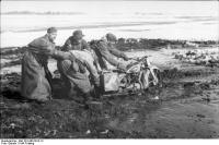 Russland, Soldaten mit Motorrad imSchlamm