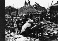 Family Sitting in Bomb Wreckage