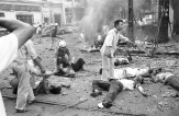Vitimas vietnamita recebem os primeiros-socorros depois que uma bomba explodiu do lado de fora da Embaixada americana em Saigon, em 30 de março de 1965. Sob a fumaça, atrás dos destroços, estão dois americanos e vários vietnamitas mortos no atentado. (AP Photo/Horst Faas)