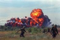 Uma bola de fogo de napalm explode próxima a tropas americanas que patrulhavam o Vietnã do Norte em 1966. (AP Photo)