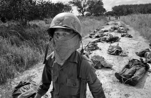 Um Observador Vietnamita usa uma máscara no rosto para se proteger do cheiro de corpos em decomposição de soldados americanos e vietnamitas mortos durante um ataque Viet Cong em uma plantação de borracha da empresa Michelin, a nordeste de Saigon, 27 de novembro de 1965. Mais de 100 corpos foram encontrados depois dos ataques de guerrilha. (AP Photo/Horst Faas)