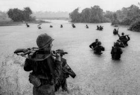 Paraquedistas Americanos do 2º Batalhão, 173 Brigada paraquedista carregam suas armas automáticas sobre as águas para atravessar um rio na chuva durante uma busca por posições Viet Gong em área de selva em Ben Cat, Vietnã do Sul em 25 de setembro de 1965.