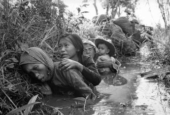 Mulheres e crianças agachadas durante fogo intenso de Viet Gongs.