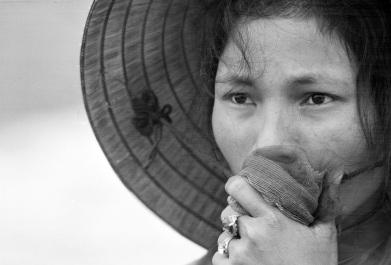 Uma jovem sul-vietnamita protege sua boa enquanto olha para uma vala comum de um relato de massacre Viet Gong. Houve exumação dos corpos em abril 1969. A esposa, pai e irmãos da mulher estavam entre os desaparecidos durante a Ofensiva de Tet, todos mortos por forças comunistas. (AP Photo/Horst Faas)